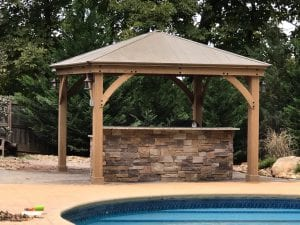outdoor stone counter with wood pergola and pool
