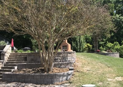 retaining wall, stone steps, and outdoor brick fireplace